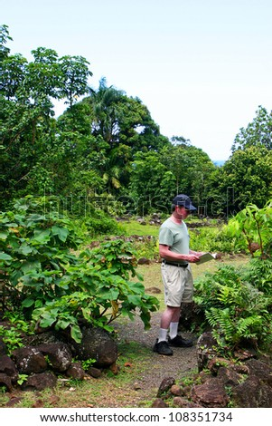 Middle-age Man Reading Brochure Limahuli National Tropical Botanical Gardens Kauai Hawaii - stock photo