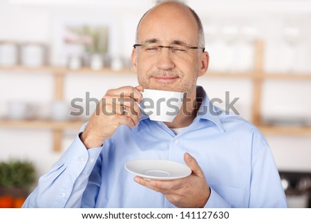 Middle age man smelling the aromatic coffee at the kitchen - stock photo