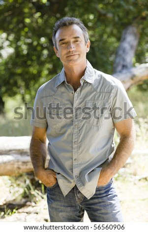 Middle Age Man Standing Outdoors With Hand in Pockets - stock photo