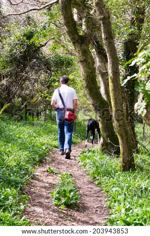 Middle age man walking a dog, Great Dane through the woods in Devon, UK, carrying a camera bag on his shoulder