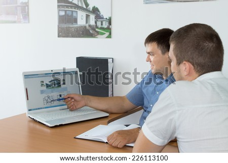 Middle Age Managers Discussing Business While Looking at their Website using Laptop Computer on the Desk. - stock photo