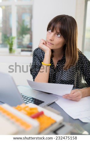 Middle Age Office Woman Thinking Something of What to Write on White Paper with Laptop on the Side. Captured Office Indoor. - stock photo