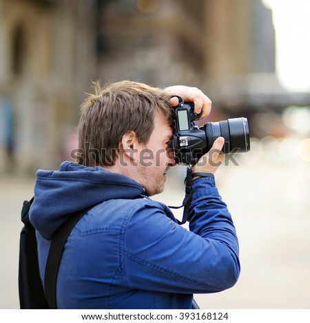 Middle age photographer taking photo with professional digital camera outdoors