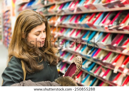 Middle age, real life woman buying shoes in a shoe store - stock photo