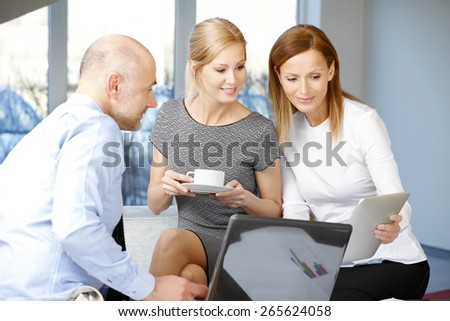 Middle age sales woman presenting her idea to sales team while they sitting at office and using laptop and digital tablet.