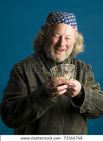middle age senior long hair wearing leather motorcycle jacket American flag bandana  happy with cash money - stock photo