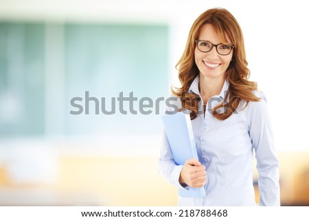 Middle age teacher standing in front of blackboard at classroom. - stock photo