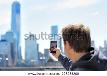 Middle age tourist taking mobile photo of skyscrapers using his smart phone   - stock photo
