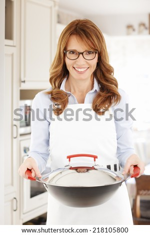 Middle age woman cooking at home.  - stock photo