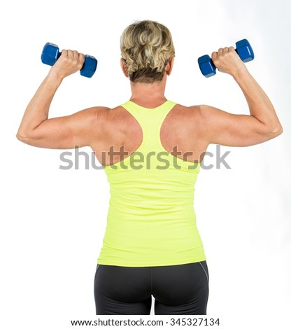 middle age woman doing arms exercises with dumbbell - stock photo
