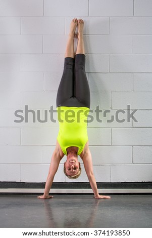 middle age woman doing handstand across wall - stock photo