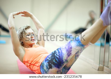 Middle age woman doing push press technique; elevated arms and legs - stock photo