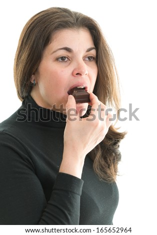 Middle age woman eating chocolate. Beautiful lady enjoying a chocolate bar. - stock photo