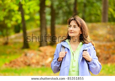 Middle age woman hiking in the autumn forest - stock photo