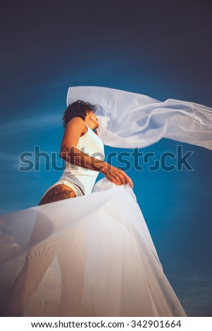 Middle age woman in white swimsuit and fluttering white fabric over blue sky.