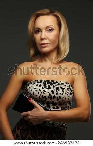 Middle age woman posing in studio. Isolated on grey