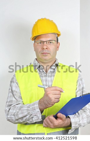 Middle Age Worker in Safety Gear Checking Clip Board - stock photo