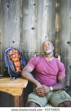 Middle-aged African American man resting in chair with backpack - stock photo