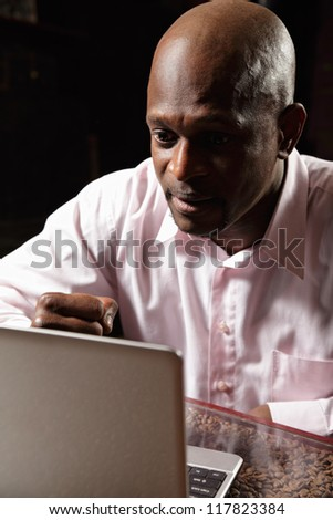 Middle-aged african guy in pink shirt sitting at laptop expressing expectance