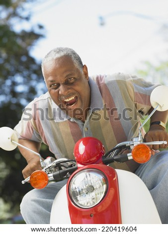 Middle-aged African man riding a scooter - stock photo