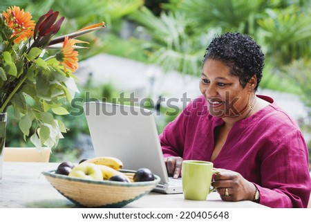 Middle-aged African woman using laptop outdoors - stock photo