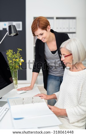 Middle Aged and Young Businesswomen Checking Some Business Documents at the Table Inside the Office. - stock photo