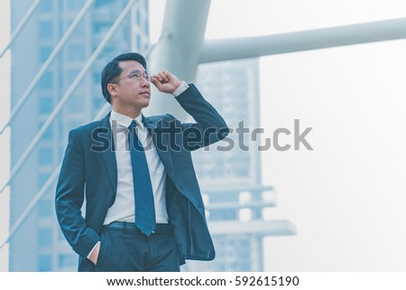 Middle-aged asian businessman holding glasses stand in modern city.Copy space