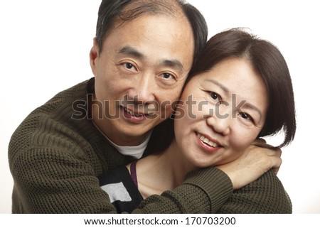 Middle aged Asian couple on white background - stock photo
