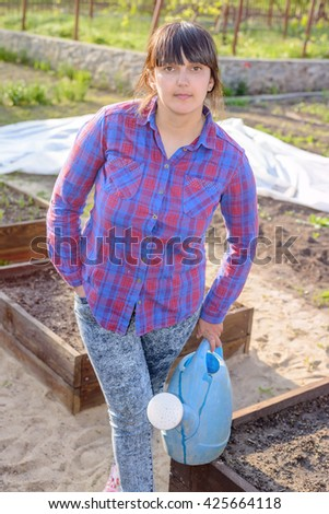 Middle-aged attractive woman doing the watering standing in the vegetable garden amongst raised beds holding a watering can