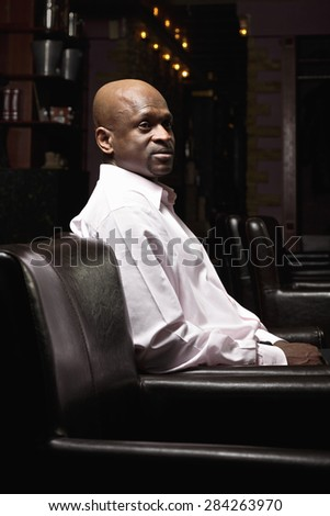 Middle-aged bald guy sitting in chair and looking sideways - stock photo