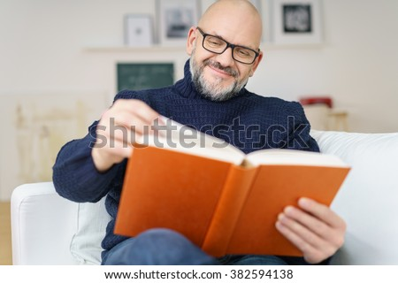 Middle-aged bald man with a goatee wearing glasses sitting on a comfortable couch enjoying a good book with a smile of pleasure - stock photo
