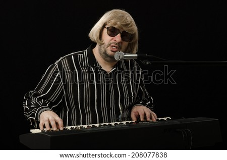 Middle-aged bearded composer playing electric organ and singing at the same time on black background