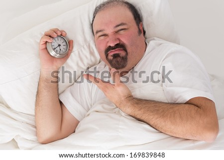 Middle-aged bearded man kept awake by noisy neighbors lying in bed grimacing and pointing to the time on his alarm clock - stock photo