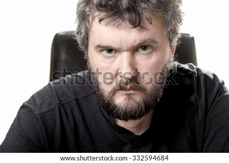 Middle-aged bearded man sits in leather chair  looking askance at the viewer.