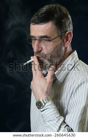 Middle aged bearded man smoking a cigarette - stock photo