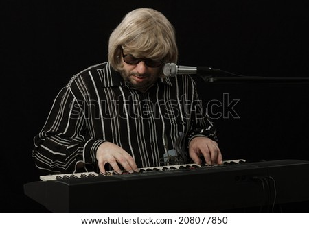 Middle aged bearded musician improvising and writing music with digital piano on black background - stock photo