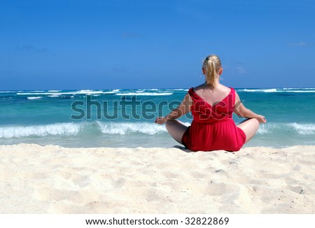 Middle-aged blond woman in red meditating on tropical beach with turquoise water, waves hitting in the white sand - stock photo