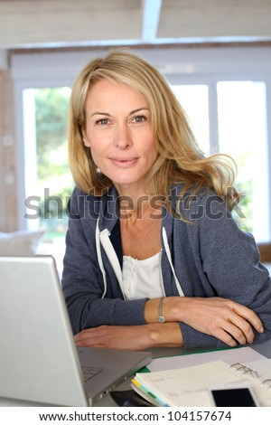 Middle aged blond woman working at home with laptop - stock photo