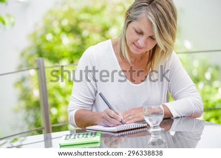 middle aged blond woman working at home without stress - stock photo