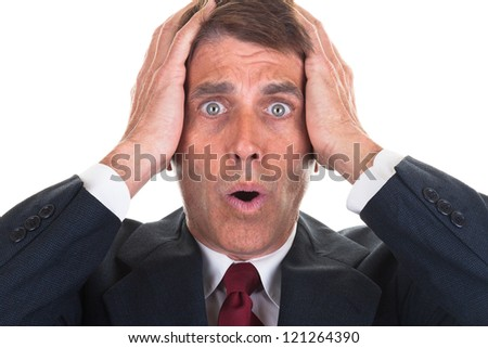 Middle aged business man holding his head in shock and surprise.