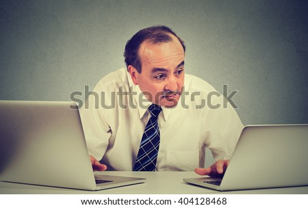 Middle aged business man multitasking working on two computers in his office  - stock photo
