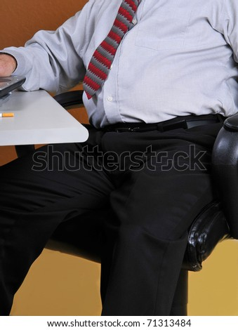 Middle aged business man sitting at his desk working. Man's poor posture and physical appearance along with seeing the butt of a cigarette may show bad lifestyle and could lead to physical problems. - stock photo