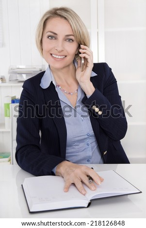Middle aged business woman in her office calling with mobile phone.