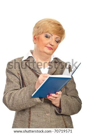 Middle aged business woman writing in personal agenda isolated on white background