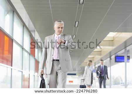 Middle aged businessman checking time with colleagues in background at railroad station - stock photo