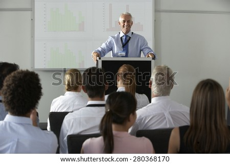 Middle Aged Businessman Delivering Presentation At Conference - stock photo