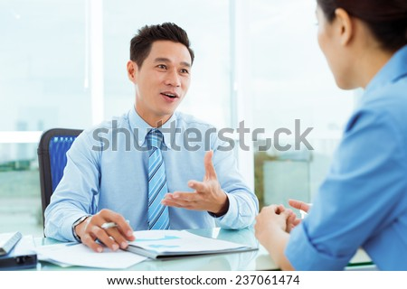 Middle-aged businessman discussing document with his female employee - stock photo