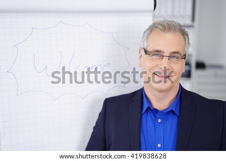 Middle-aged businessman doing a presentation in the office standing alongside a flip chart with the word Welcome smiling at the camera - stock photo