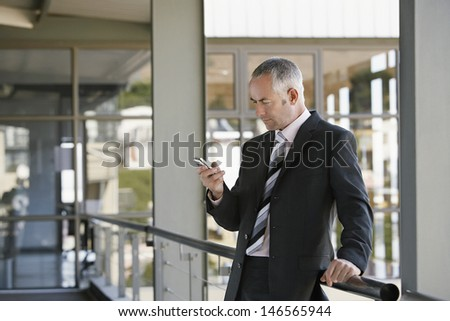 Middle aged businessman leaning on railing while using mobile phone in office - stock photo