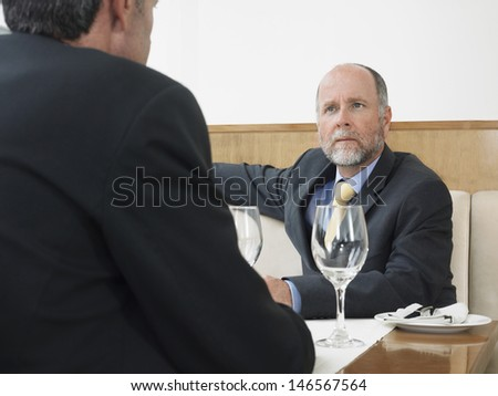 Middle aged businessman listening to male colleague in restaurant - stock photo